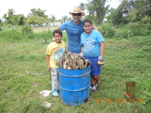 Ron Berezan with two children of a local producer about to make a batch of biochar with a TLUD design.